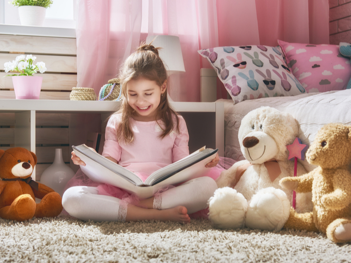 girl reading book with teddy bears