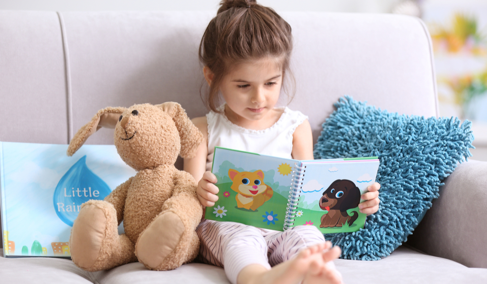 child reading book with stuffed animals
